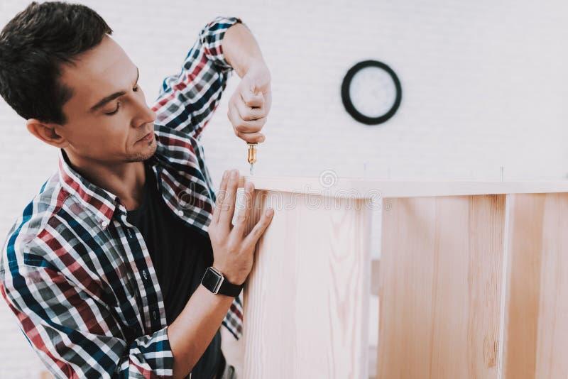 在家装配木书架的年轻人 免版税图库摄影