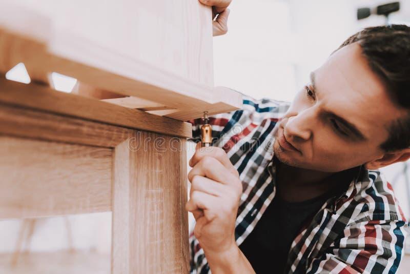 在家装配木书架的年轻人 免版税库存图片