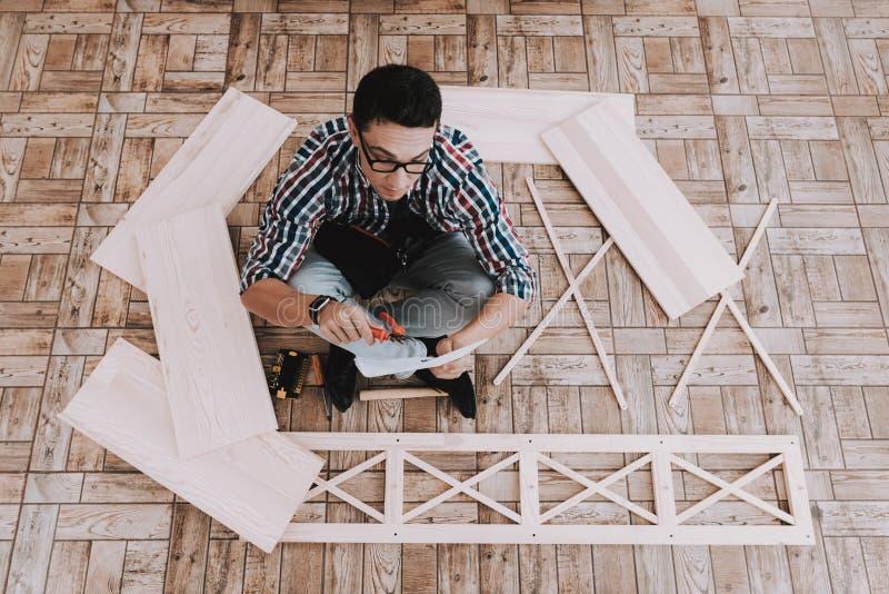 在家装配木书架的年轻人 图库摄影