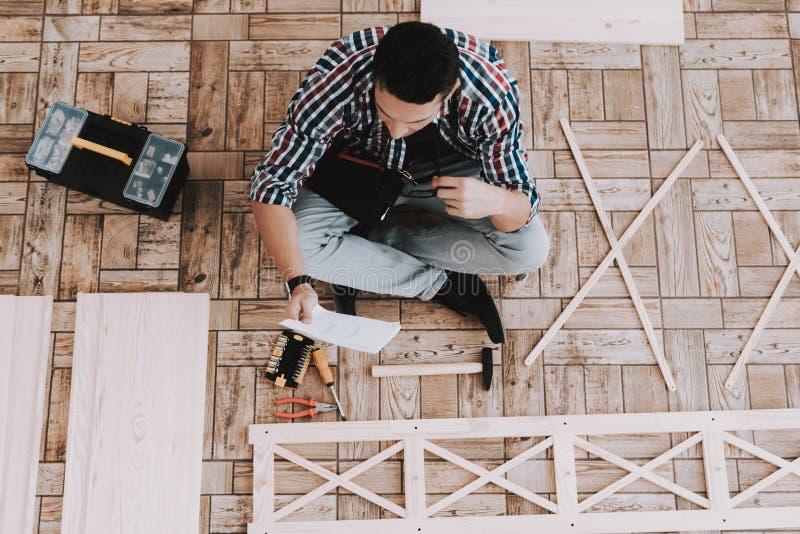 在家装配木书架的年轻人 库存照片