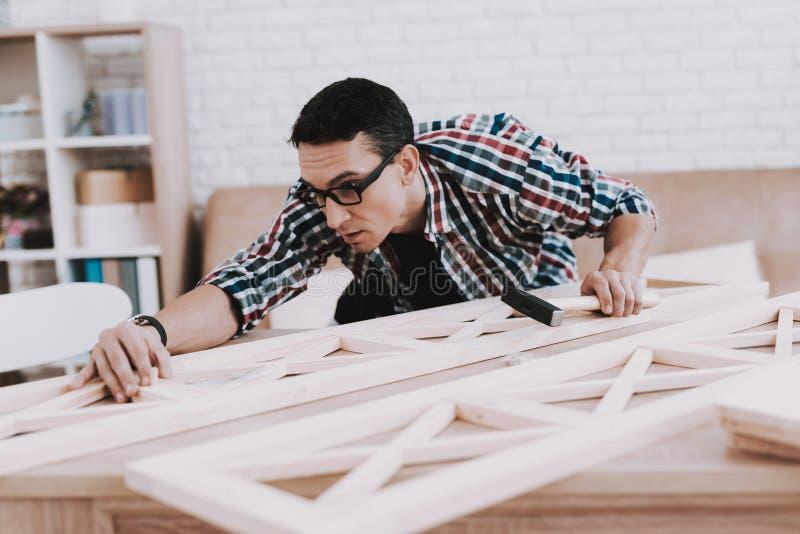在家装配木书架的年轻人 免版税库存照片