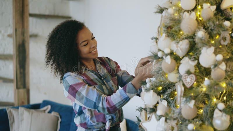 在家装饰圣诞树的可爱的年轻非洲妇女为Xmas庆祝做准备 免版税库存图片