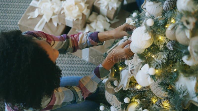 在家装饰圣诞树的可爱的年轻非洲妇女顶视图为Xmas庆祝做准备 免版税图库摄影