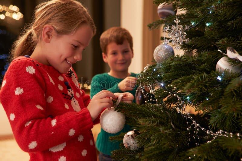在家装饰圣诞树的孩子 免版税图库摄影