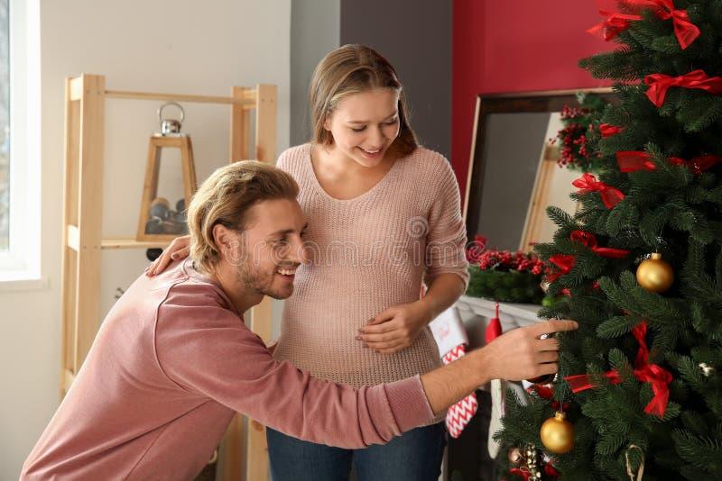在家装饰圣诞树的年轻怀孕的夫妇 免版税库存照片