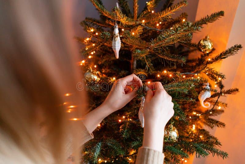 在家装饰圣诞树的愉快的年轻女人 在房子内部的寒假 金黄和白色圣诞节快乐 免版税库存图片