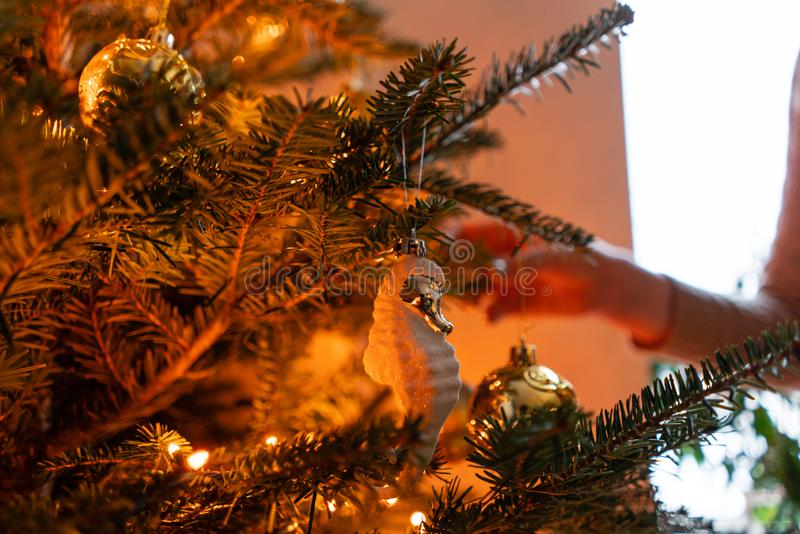 在家装饰圣诞树的愉快的年轻女人 在房子内部的寒假 金黄和白色圣诞节快乐 库存图片