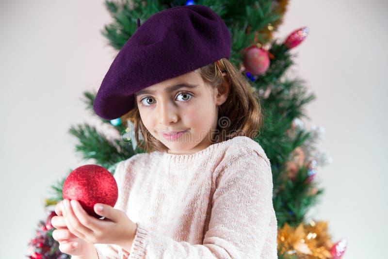 在家装饰圣诞树的愉快的矮小的女孩 免版税库存图片