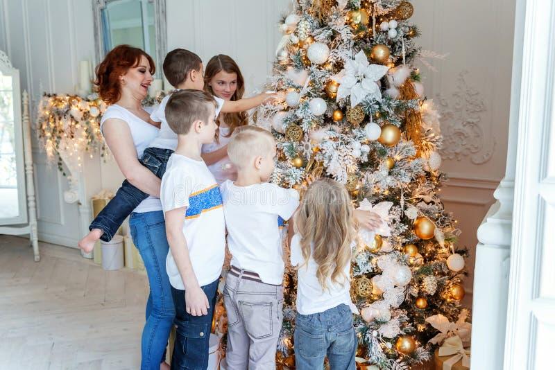 在家装饰圣诞树的母亲和五个孩子 库存图片