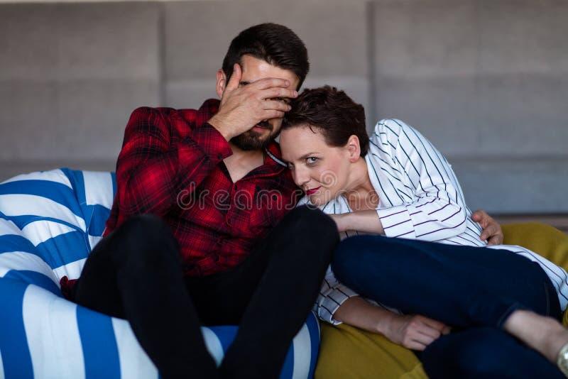 在家观看一部电影用玉米花的年轻夫妇 免版税库存照片