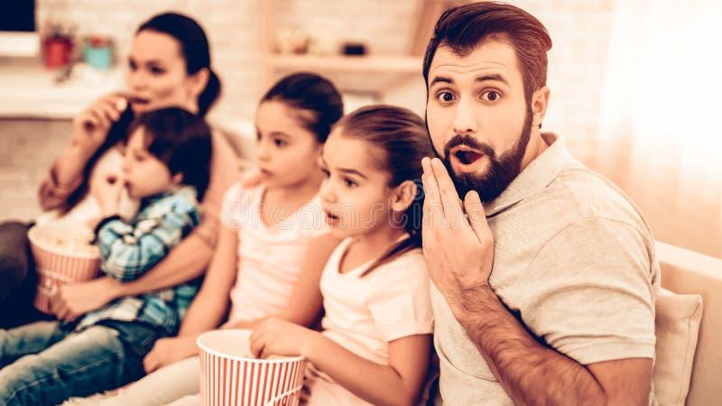 在家观看可怕电影的快乐的家庭 免版税图库摄影