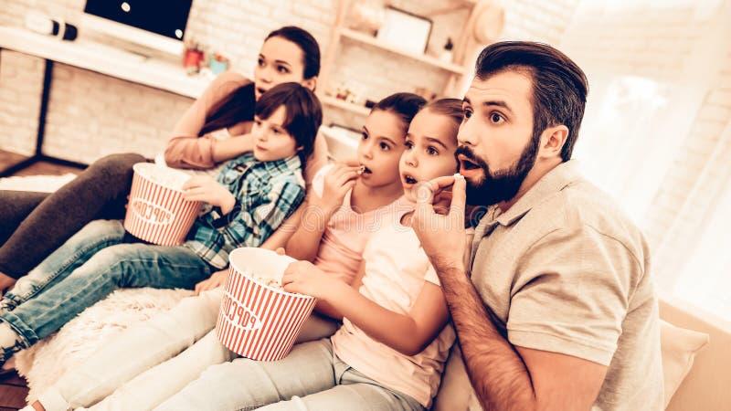 在家观看可怕电影的快乐的家庭 免版税库存照片