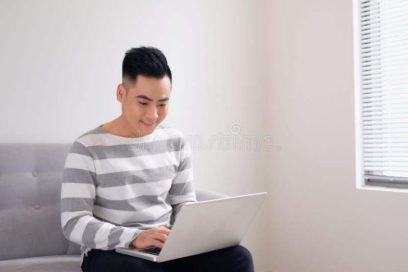 在家观看和研究计算机膝上型计算机的愉快的微笑的年轻人 库存照片