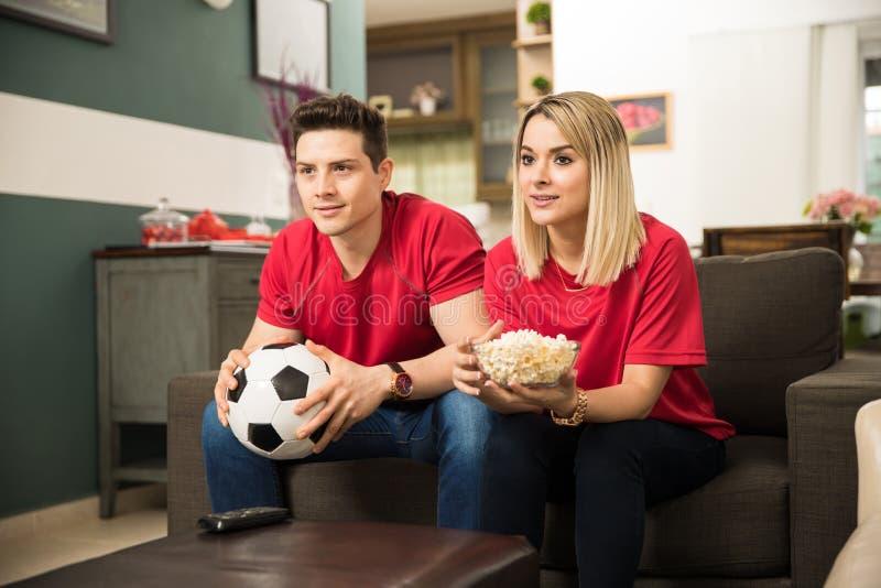 在家观看足球赛的夫妇 免版税库存照片