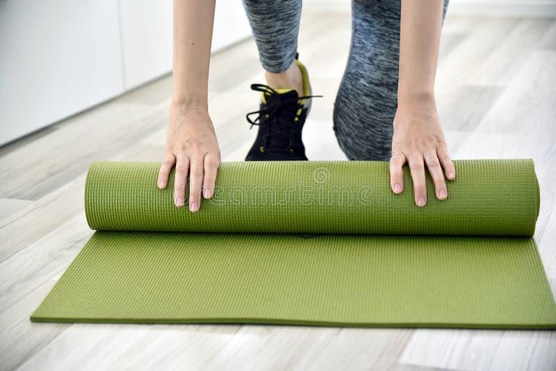 在家解决以后的妇女折叠的瑜伽或健身席子 免版税图库摄影
