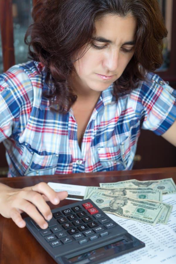 在家计数金钱的拉丁妇女付帐单 免版税库存照片