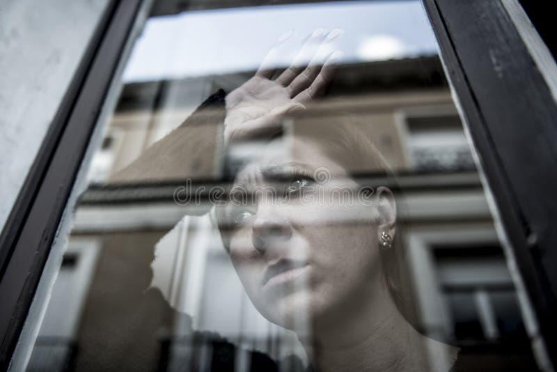 在家认为和感觉哀伤的遭受的消沉窗口的年轻美丽的妇女画象的剧烈的关闭看depresse 库存图片