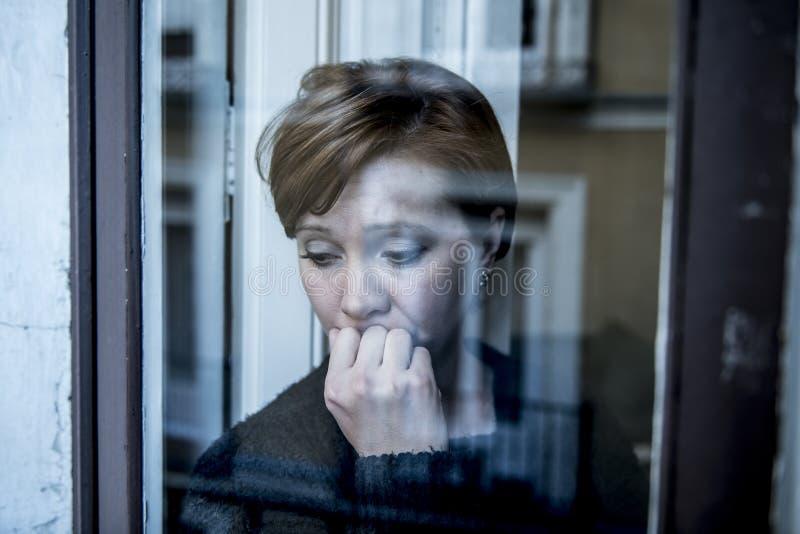 在家认为和感觉哀伤的遭受的消沉窗口的年轻美丽的妇女画象的剧烈的关闭看depresse 免版税图库摄影