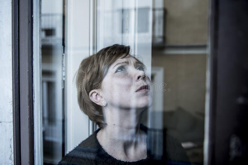在家认为和感觉哀伤的遭受的消沉窗口的年轻美丽的妇女画象的剧烈的关闭看depresse 库存照片