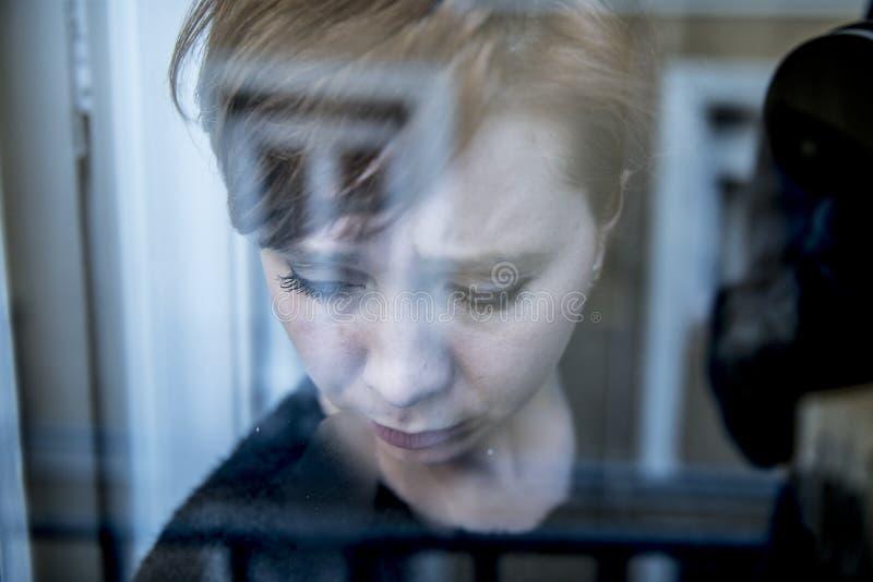 在家认为和感觉哀伤的遭受的消沉窗口的年轻美丽的妇女画象的剧烈的关闭看depresse 免版税库存照片
