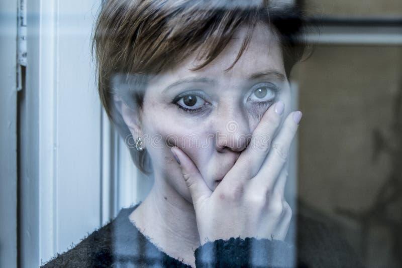 在家认为和感觉哀伤的遭受的消沉窗口的年轻美丽的妇女画象的剧烈的关闭看depresse 免版税库存图片