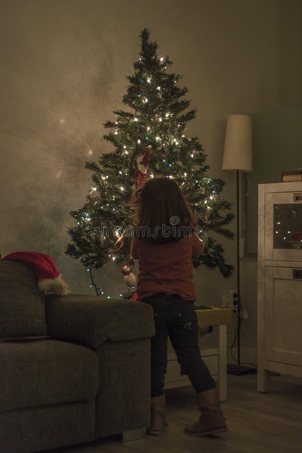 在家设定与光和ornam的女孩圣诞树 免版税库存照片