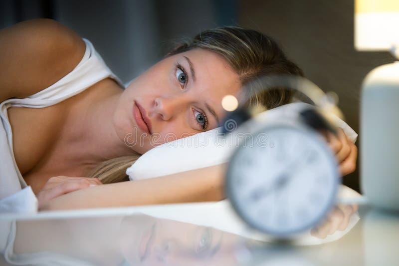 在家说谎在床上的美好的年轻被用尽的妇女遭受的失眠在卧室 免版税库存照片