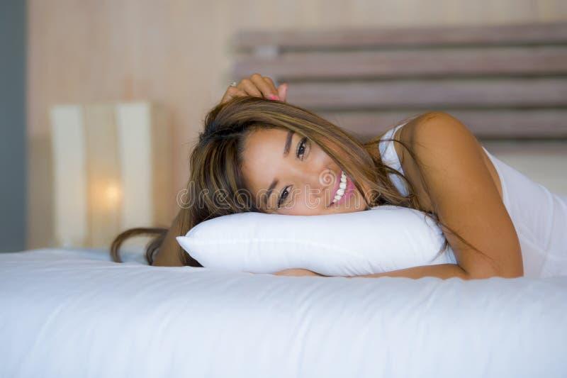 在家说谎在床卧室摆在放松和微笑的年轻可爱的美丽和愉快的亚裔拉丁混杂的妇女快乐 免版税库存照片