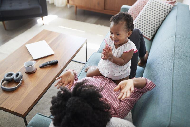 在家说谎在沙发的母亲打与小女儿的拍的比赛 免版税库存图片