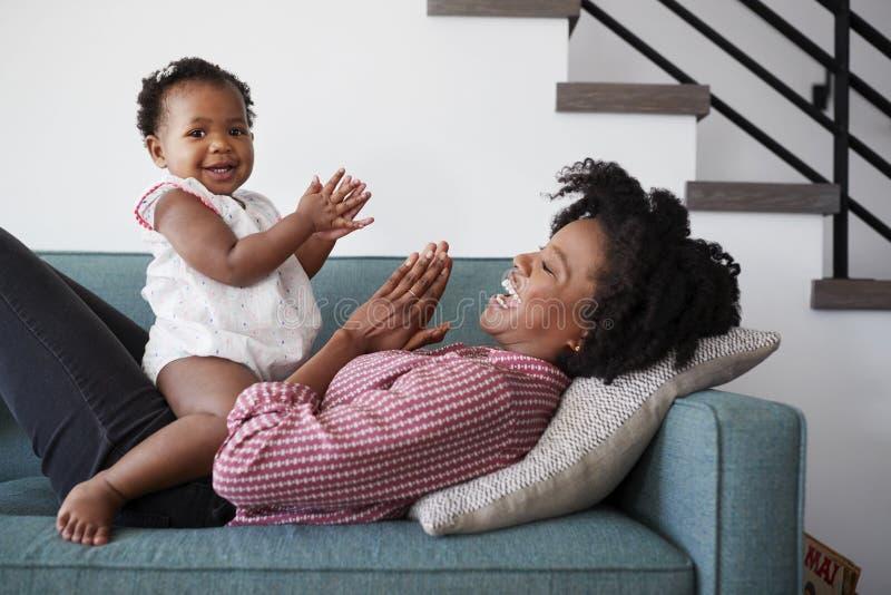 在家说谎在沙发的母亲打与小女儿的拍的比赛 免版税库存照片