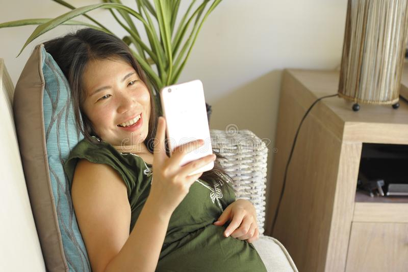 在家说谎客厅沙发长沙发使用愉快的手机和comf的互联网的年轻美丽和轻松的亚裔中国妇女 免版税库存图片
