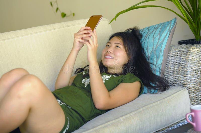 在家说谎客厅沙发长沙发使用愉快的手机和comf的互联网的年轻美丽和轻松的亚裔中国妇女 免版税库存照片