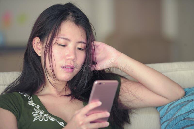 在家说谎客厅沙发长沙发使用愉快的手机和comf的互联网的年轻美丽和轻松的亚裔中国妇女 图库摄影