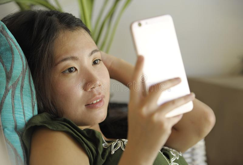 在家说谎客厅沙发长沙发使用愉快的手机和comf的互联网的年轻美丽和轻松的亚裔中国妇女 库存照片