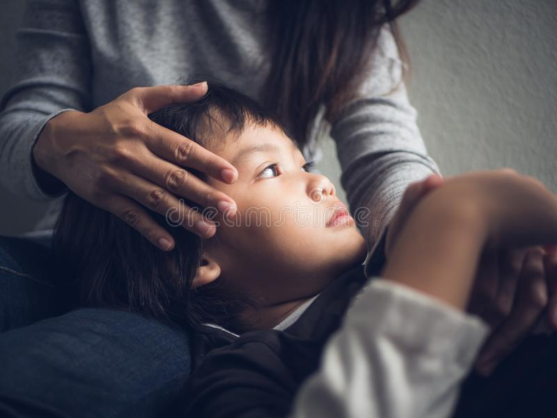 在家说谎由他的母亲的特写镜头哀伤的小男孩 图库摄影