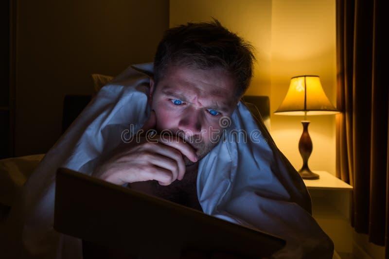 在家读与片剂个人计算机的英俊的年轻人说谎在床在晚上 他疲乏并且要睡觉 免版税库存图片