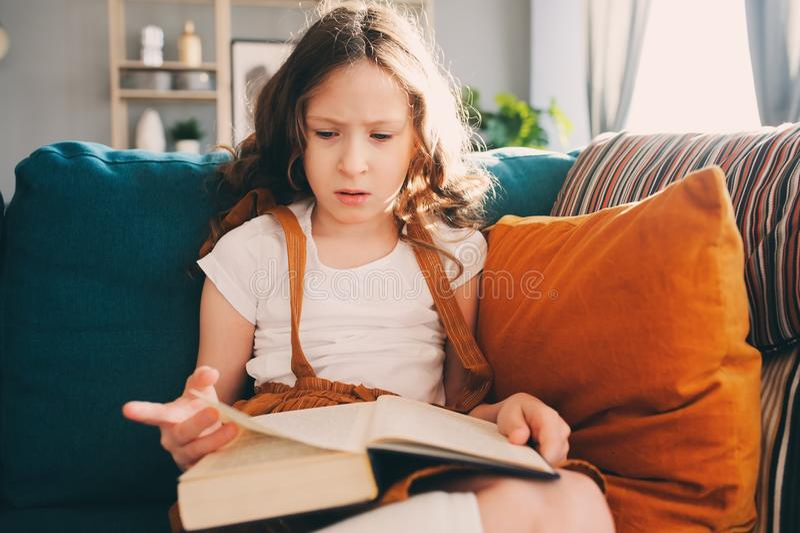 在家读有趣的书的被集中的孩子女孩 库存图片
