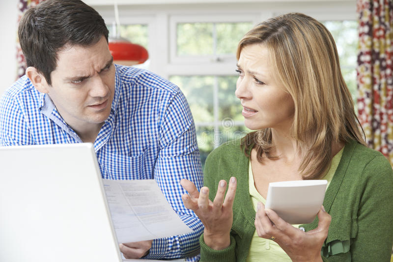 在家谈论担心的夫妇国内财务 库存照片