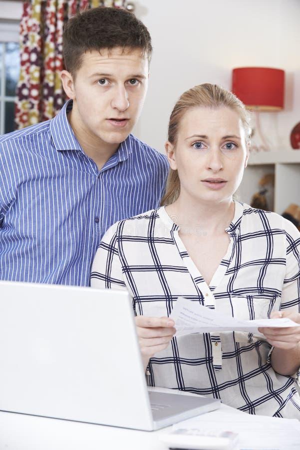 在家谈论担心的夫妇国内财务 库存图片