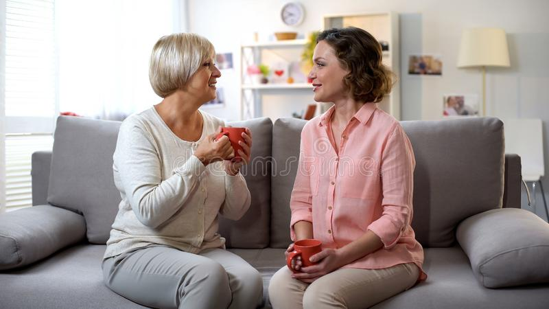 在家谈话的母亲和的女儿,放松在有咖啡的沙发,信任 免版税库存图片