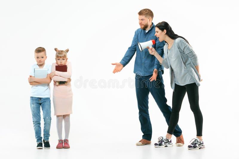 在家责骂他们的孩子的恼怒的父母 免版税库存照片