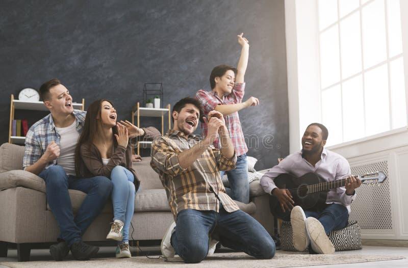 在家跳舞年轻的朋友有党,弹吉他,唱歌和 图库摄影