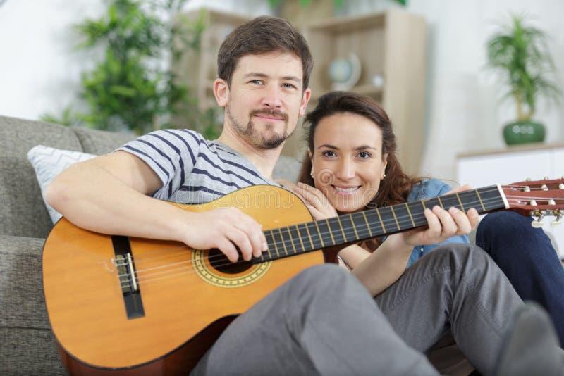 在家过浪漫夜晚的情侣,男人弹吉他 免版税库存照片
