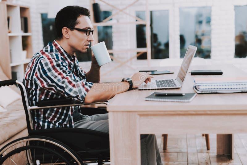在家运转的轮椅的年轻残疾人 免版税库存图片