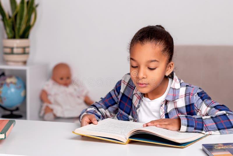 在家选址在桌上和做他的家庭作业的女小学生 免版税库存图片