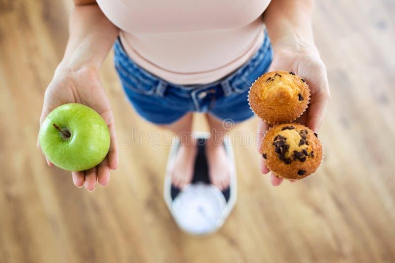 在家选择在果子和甜点之间的少妇在秤 概念饮食 免版税库存照片