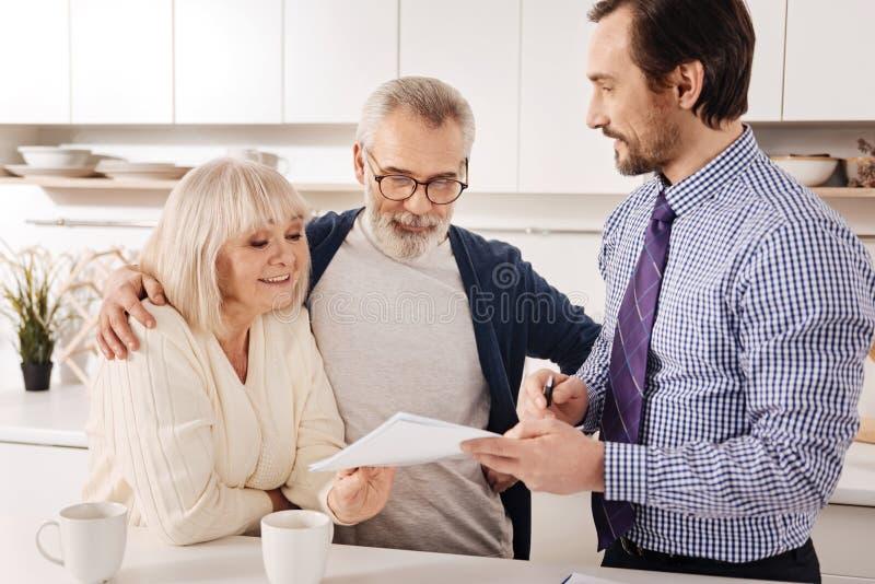 在家遇见财政顾问的正面老化夫妇所有者 库存照片
