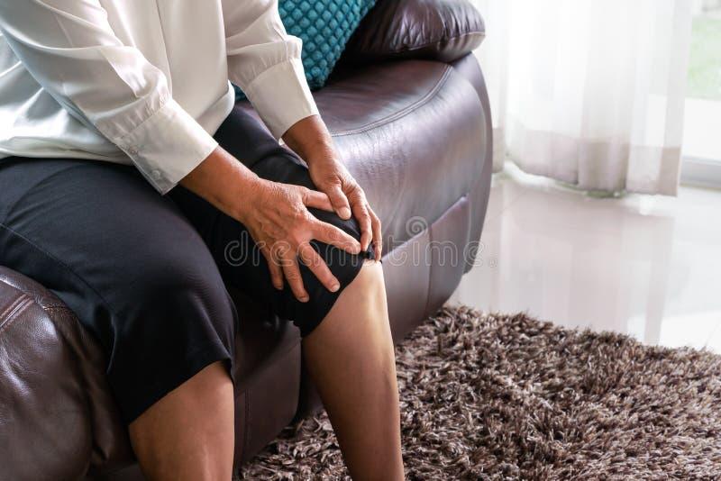 在家遭受膝盖痛苦的老妇人,健康问题概念 免版税库存照片