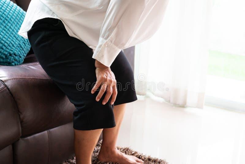 在家遭受膝盖痛苦的资深妇女,健康问题概念 免版税库存照片