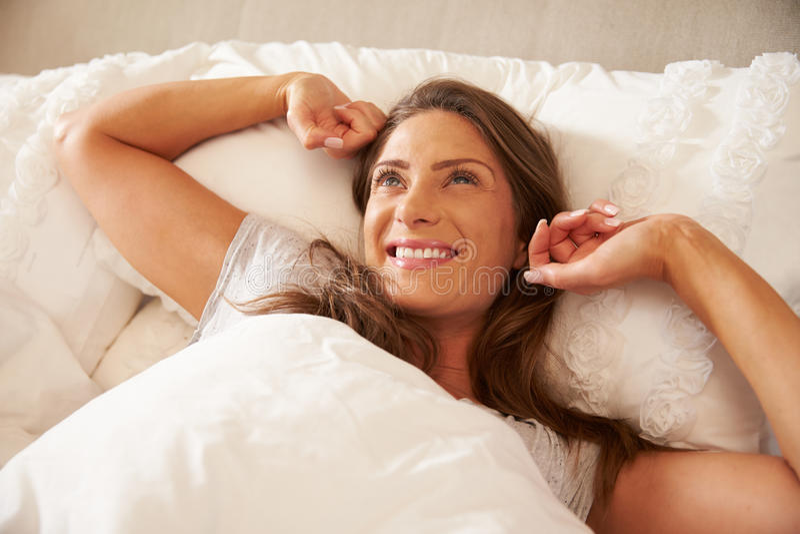 在家醒和舒展在床上的妇女 免版税库存照片